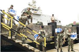 Mariniers en Arubaanse miliciens laden water voor noodhulp op Dominica.
